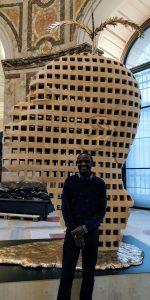 Aimé Mpane devant sa sculpture, réalisée en 2016