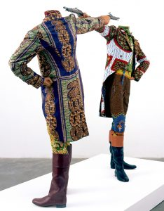 Photographie d'une oeuvre de l'expo IncarNations (BOZAR, 2019): Yinka Shonibare CBE, How to blow up two heads at once, Installation, 2 mannequins, wax allemand imprimé en coton, bottes en cuir, socle, 2006, 175 x 245 x 122 cm © Yinka Shonibare, courtesy of Stephen Friedman Fine Art
